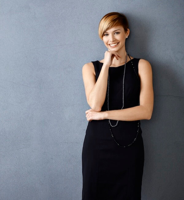 A smiling woman in a long, black dress with short hair