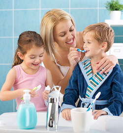 Mom, son, and daughter with brushing their teeth together in the bathroom