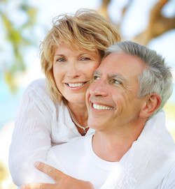 A mature couple smiling and embracing outside