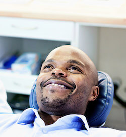 A dental patient looking relaxed, lying back, and smiling