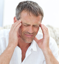 Man having a headache and holding his temples