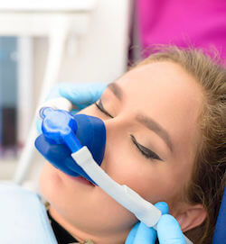 Beautiful woman getting inhalation sedation at dental clinic